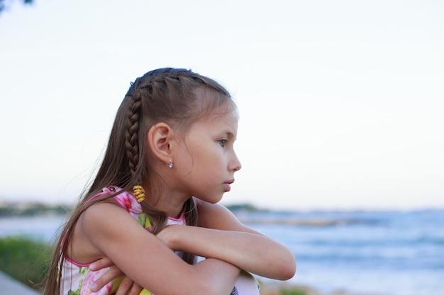 Portret młodej dziewczyny siedzącej na plaży, patrząc od horyzontu rano