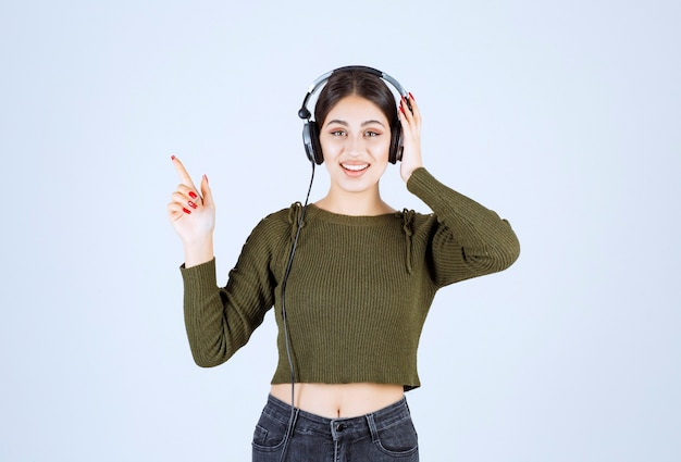 Portret młodej dziewczyny słucha muzyki i wskazuje w słuchawkach.