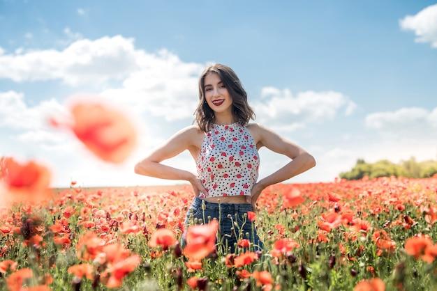 Portret młodej dziewczyny spaceru w polu maku w okresie letnim. ciesz się przyrodą