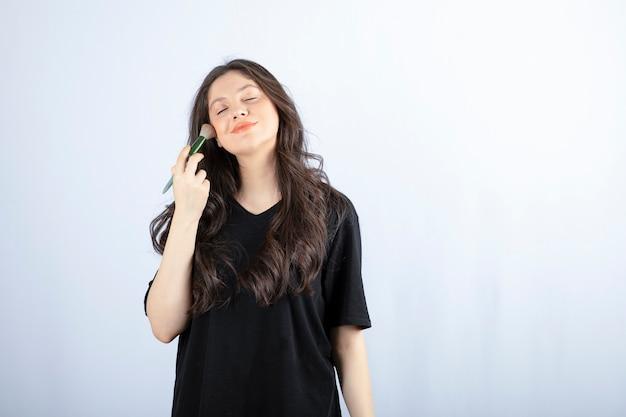 Portret młodej dziewczyny, stosując rumieniec na jej policzkach na białym tle.