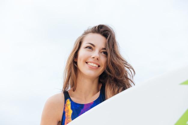 Portret młodej dziewczyny surfer z seksownym dopasowanym ciałem w stroju kąpielowym trzymającym deskę surfingową