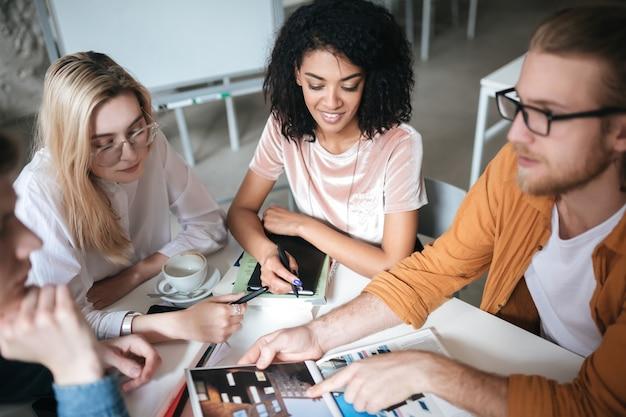 Portret młodej dziewczyny szczęśliwy z ciemnymi kręconymi włosami siedzi z przyjaciółmi przy stole i omawiając nowy dziennik. grupa młodych ludzi pracujących razem