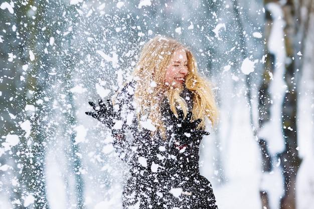 Portret młodej dziewczyny teen zimą. piękna radosna modelka dziewczyna śmieje się i dobrze się bawi w winter park