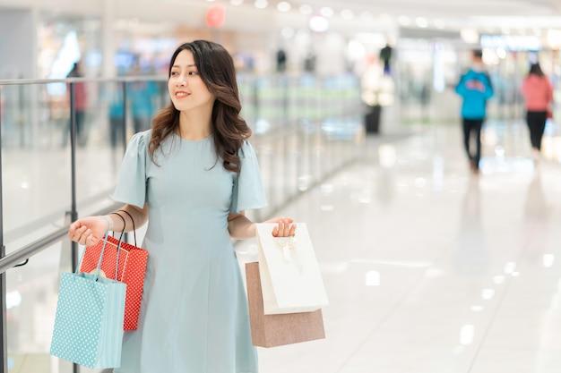 Portret młodej dziewczyny trzymając torbę na zakupy spaceru w centrum handlowym