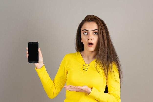 Portret młodej dziewczyny trzymającej telefon z zaskoczonym wyrażeniem na szarej ścianie.