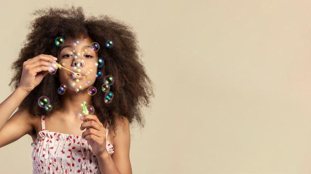Portret młodej dziewczyny urocze pozowanie podczas gry z baniek mydlanych