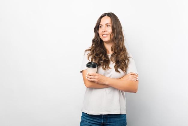 Portret młodej dziewczyny uśmiechający się trzymając papierowy kubek kawy.