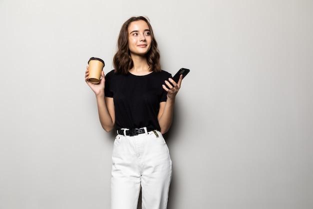 Portret młodej dziewczyny uśmiechnięte w koszuli wiadomości sms na telefon komórkowy i trzymając filiżankę kawy na wynos