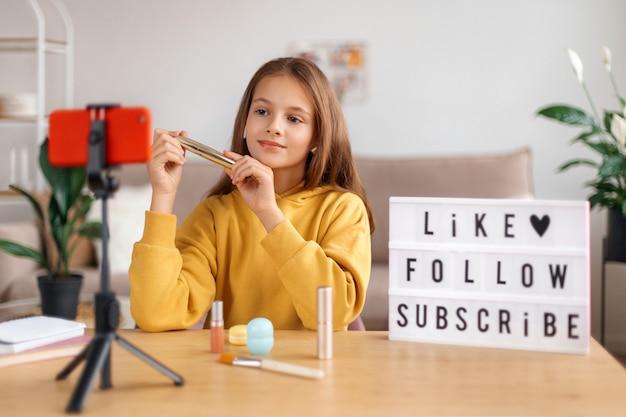 Portret młodej dziewczyny vlogger nagrywa transmisję wideo na żywo na aparat w smartfonie w domu