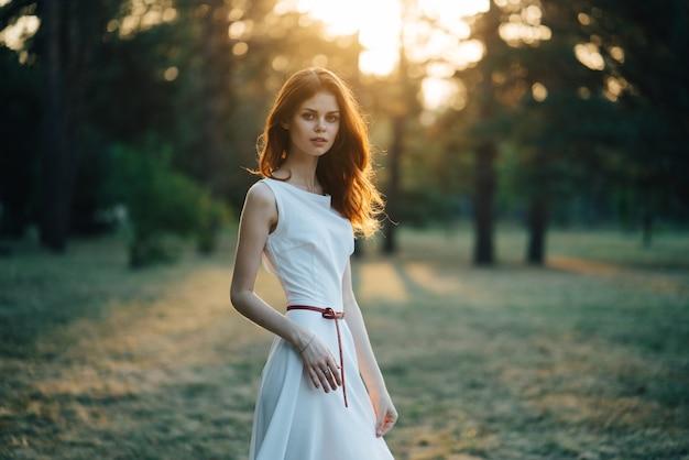 Portret młodej dziewczyny w białej sukni w promieniach słońca