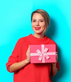 Portret młodej dziewczyny w czerwonym swetrze z pudełkiem na niebieskim tle