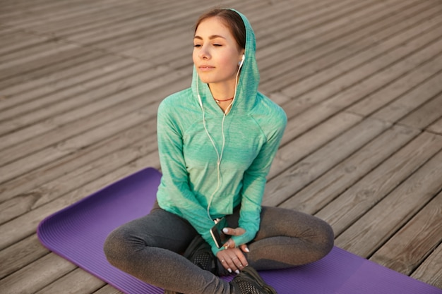 Portret młodej dziewczyny w jasnej odzieży sportowej, słuchając ulubionej piosenki na słuchawkach po porannej jodze i cieszyć się słońcem.