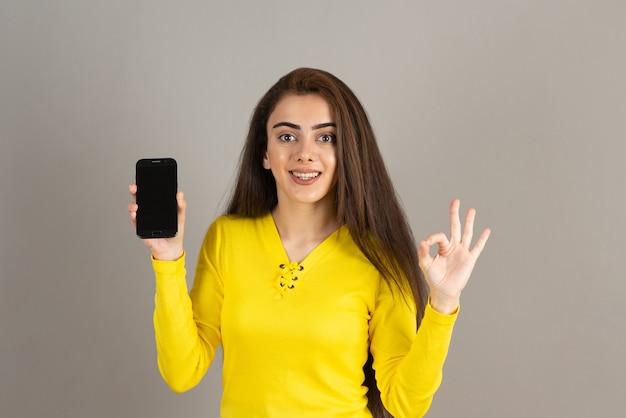 Portret młodej dziewczyny w kolorze żółtym, trzymając telefon na szarej ścianie.