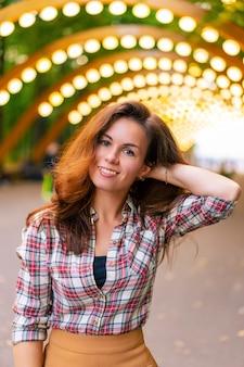 Portret młodej dziewczyny w koszuli w parku sokolniki w moskwie pod łukiem z latarniami