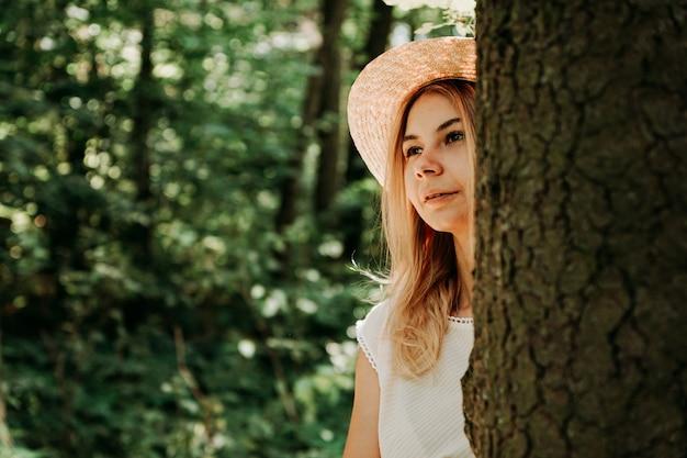 Portret młodej dziewczyny w lesie. wygląda zza pnia drzewa