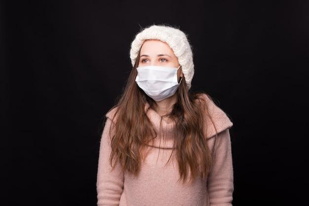 Portret młodej dziewczyny w masce medycznej na białym tle na czarnej ścianie.