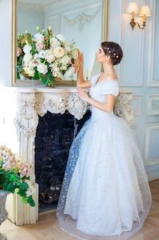 Portret młodej dziewczyny w pięknej sukience we wnętrzu, kobiecego piękna