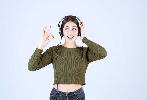 Portret młodej dziewczyny w słuchawkach, słuchając muzyki i dając znak ok.