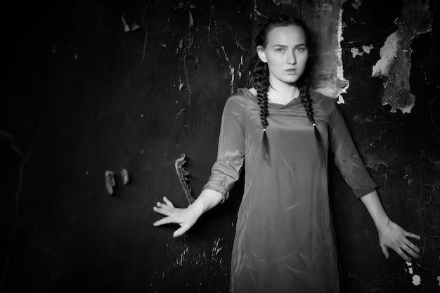 Portret młodej dziewczyny w starym domu ze spalonymi ścianami