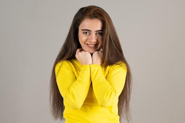 Portret młodej dziewczyny w żółtej górze patrząc i uśmiechając się na szarej ścianie.