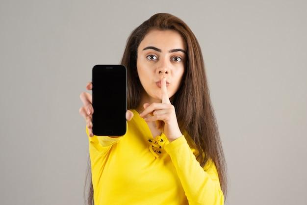 Portret młodej dziewczyny w żółtej górze pozowanie z telefonem komórkowym na szarej ścianie.