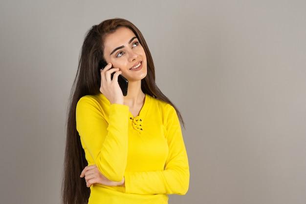 Portret młodej dziewczyny w żółtej górze rozmawia z telefonem komórkowym na szarej ścianie.