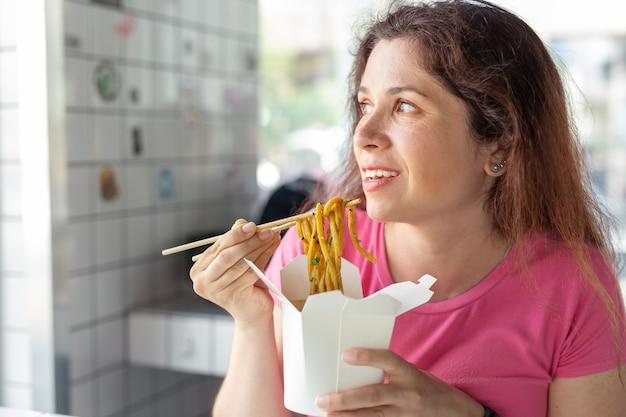 Portret młodej dziewczyny wesołej jedzenia makaronu chińskiego w kawiarni i patrząc przez okno. pojęcie zdrowej kuchni azjatyckiej.