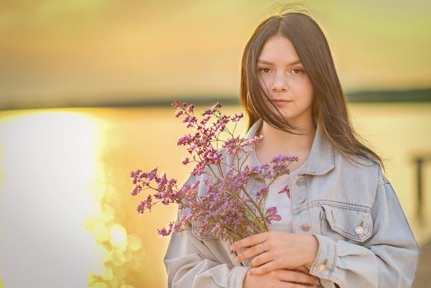 Portret młodej dziewczyny z bukietem kwiatów w dłoniach przed zachodem słońca.