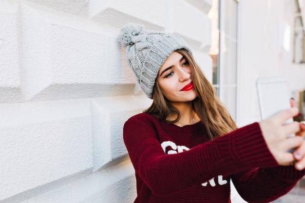 Portret młodej dziewczyny z długimi włosami dokonywanie selfie na szarej ścianie. nosi dzianinową czapkę i ma czerwone usta.