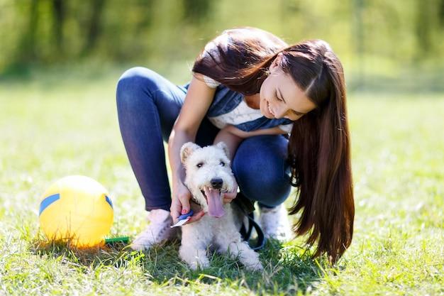Portret młodej dziewczyny z foksterierowym psem na świeżym powietrzu w parku