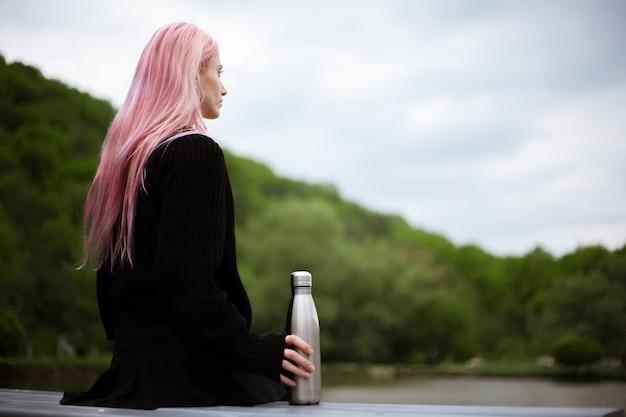 Portret młodej dziewczyny z różowymi włosami siedzi w parku z butelką termo w ręku.