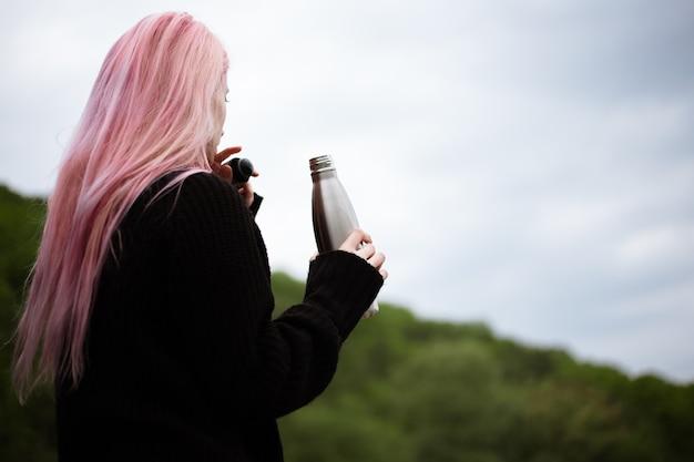 Portret młodej dziewczyny z różowymi włosami, trzymając stalową butelkę termiczną.