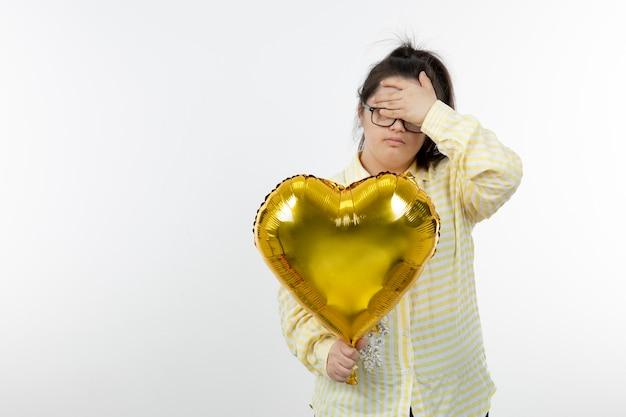 Portret młodej dziewczyny z zespołem downa, trzymając balon w kształcie serca