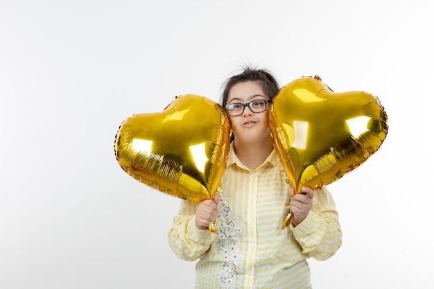 Portret młodej dziewczyny z zespołem downa, trzymając balony w kształcie serc