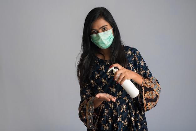 Portret młodej dziewczyny za pomocą lub dezynfekujący żel z butelki do czyszczenia rąk.