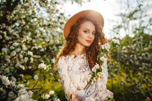 Portret młodej dziewczyny zabawy w jasny, słoneczny wiosenny dzień i zapach kwitnących białych kwiatów na jabłoni. kobieta w białej sukni i beżowym kapeluszu w parku. koncepcja wiosny.