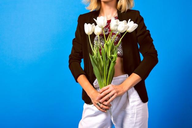Portret młodej eleganckiej kobiety z jasnym makijażem i ciemną marynarką, trzymając białe kwiaty