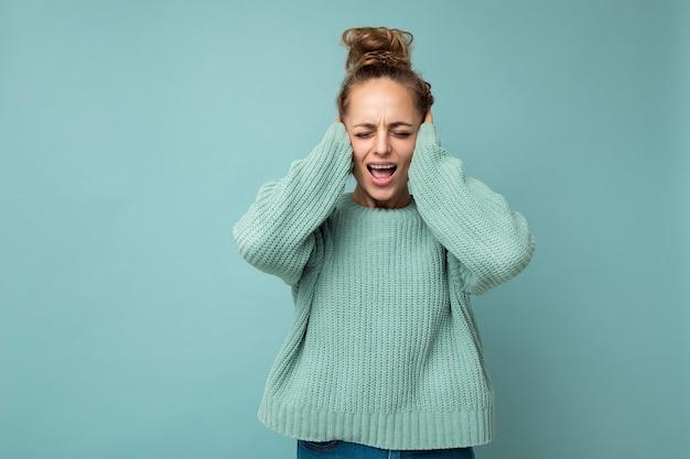 Portret młodej emocjonalnej atrakcyjnej blondynki ze szczerymi emocjami ubrana w casualową niebieską koszulkę
