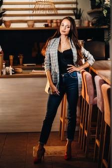 Portret młodej europejskiej dziewczyny z długimi włosami w kawiarni w wieczornym świetle, wysoka dziewczyna w kurtce z długimi włosami w kawiarni.