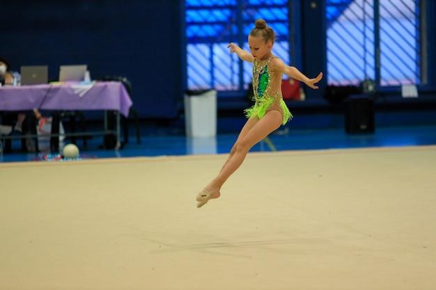 Portret młodej gimnastyczki portret letniej dziewczynki w zawodach gimnastyki rytmicznej o wysokiej...