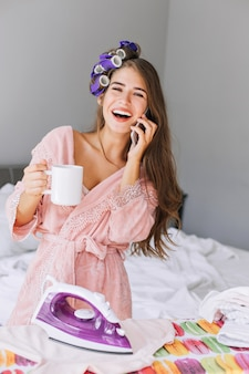 Portret młodej gospodyni z długimi włosami w różowym szlafroku i lokówce na głowie przy prasowaniu w domu. trzyma kubek, rozmawia przez telefon i się śmieje.