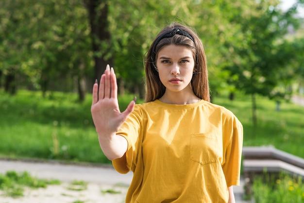 Portret młodej i pięknej dziewczyny rasy kaukaskiej pokazującej znak stop