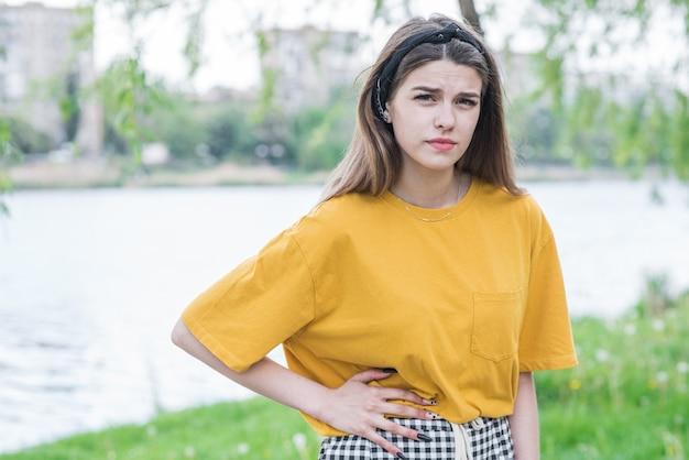 Portret młodej i pięknej kaukaskiej dziewczyny, która ma ból brzucha
