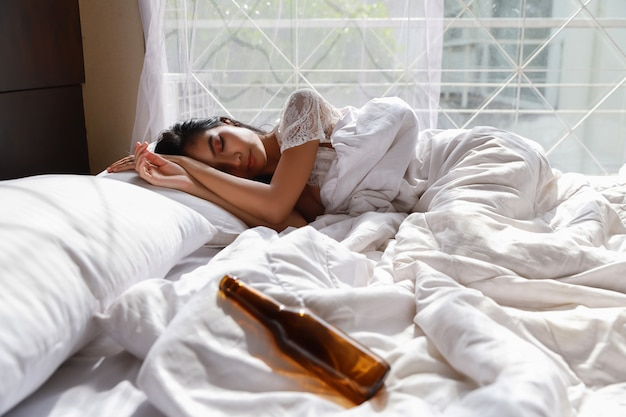 Portret młodej i pięknej pijanej kobiety w białej bieliźnie bielizna nocna nieprzytomny w łóżku po wypiciu zbyt dużej ilości alkoholu z imprezy. młoda kobieta długie włosy, leżąc na łóżku w sypialni i obudź się późno