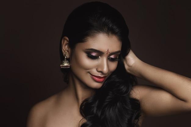 Portret młodej indyjskiej kobiety z pięknym makijażem i fryzurą na brązowej ścianie