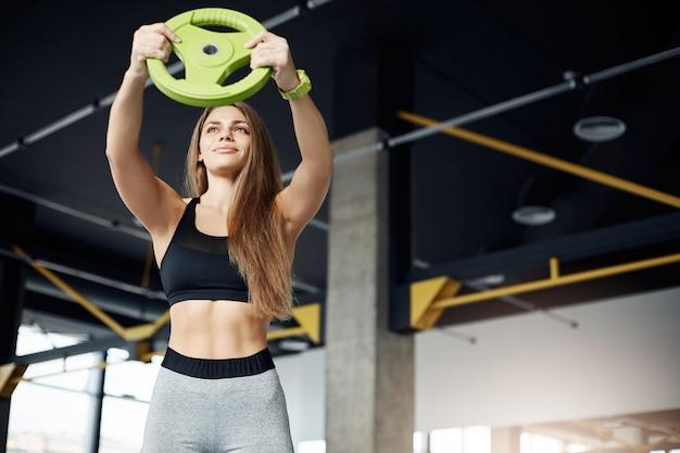 Portret młodej instruktorki fitness trenującej ramiona z dyskiem z hantlami, wyglądającej na silną i pewną jej idealnego brzucha