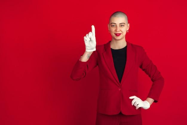 Portret młodej kaukaskiej łysej kobiety na czerwonej ścianie