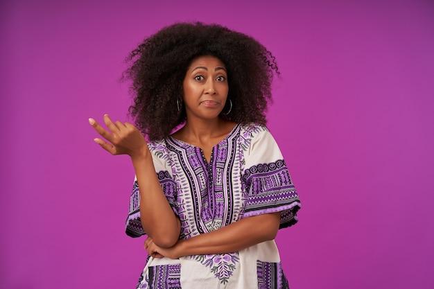 Portret młodej kędzierzawej damy na co dzień z ciemną skórą w białej wzorzystej koszuli unoszącej dłoń zmieszana z uniesionymi brwiami, stojąc na fioletowo