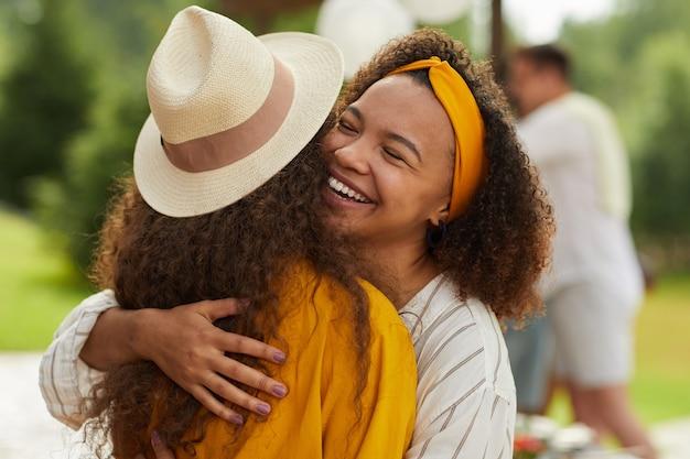 Portret młodej kobiety african-american przytulanie przyjaciela i uśmiechnięty radośnie, ciesząc się imprezą na świeżym powietrzu w lecie