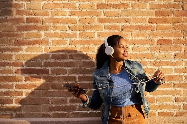 Portret młodej kobiety african american ze słuchawkami do słuchania muzyki ze swojego telefonu komórkowego